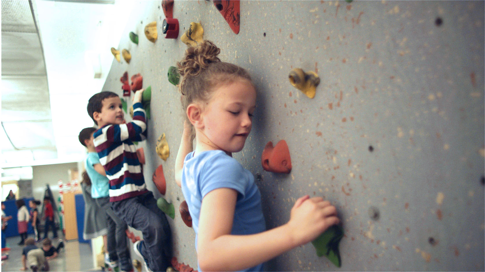 Several kindergarteners climbing a rock wall in a private school