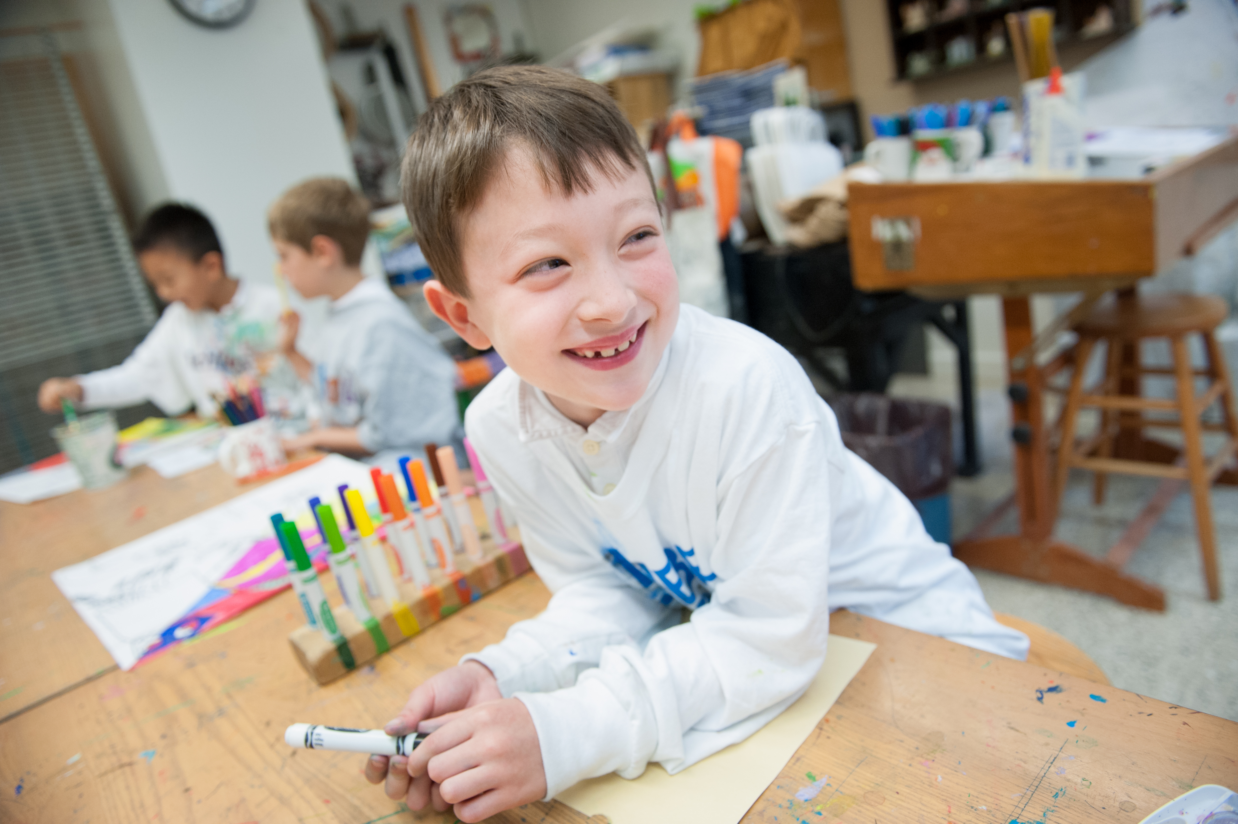 A student excited by a drawing project in a private pre-kindergarten art room