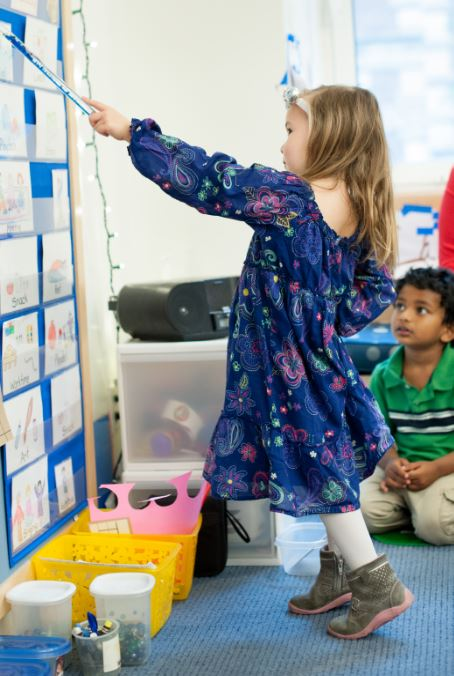 Two nursery school students learning from a learning wall